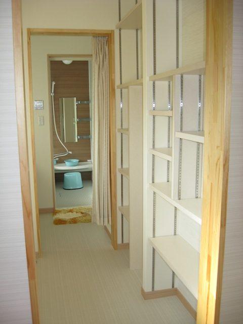 浴室に行く通路に収納棚を設けました。買い置きの洗剤や個別の衣類を収納できます。